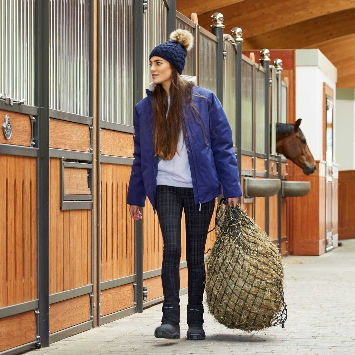 Girl carrying a hay bag while mucking out